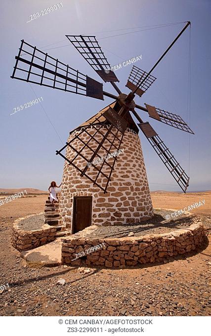 Woman posing near the windmill, Antigua, Fuerteventura, Canary Islands, Spain, Europe