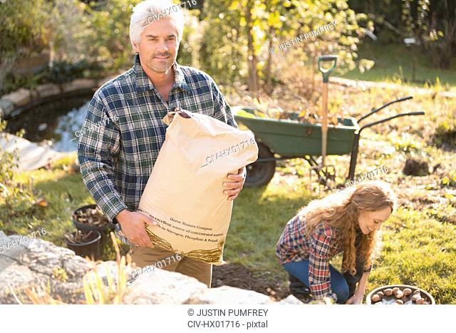 Portrait couple gardening holding potting soil in autumn garden