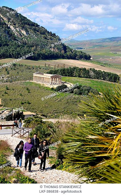 Four tourists with the view onto the Temple of Segesta in the background, Trapani, Sicily, Italy