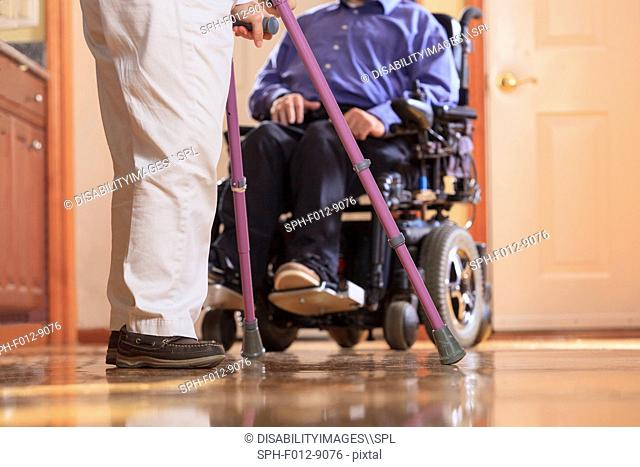 Woman with Cerebral Palsy using crutches and her husband with Cerebral Palsy in a motorized wheelchair