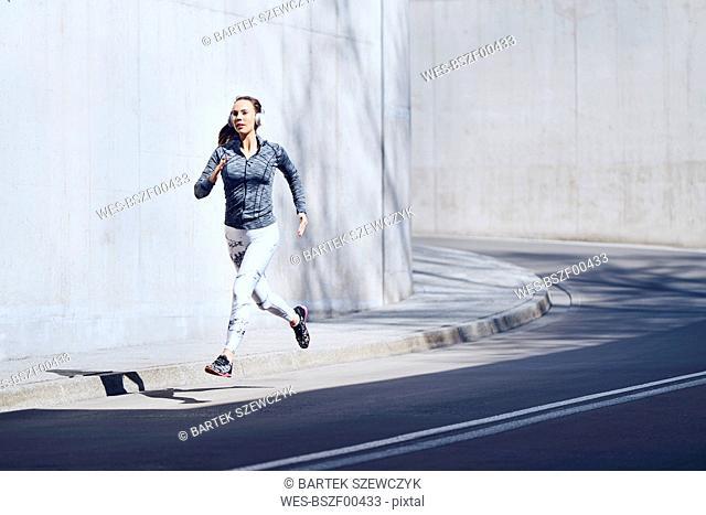 Female jogger with headphones on street