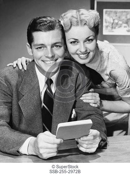 Portrait of a young couple holding a bank book