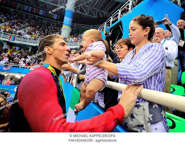 Gold medalist Michael Phelps of the USA reaches out to kiss son Boomer held by his fiancée Nicole Johnson (R) at the medal ceremony of the Men's 200m Butterfly...