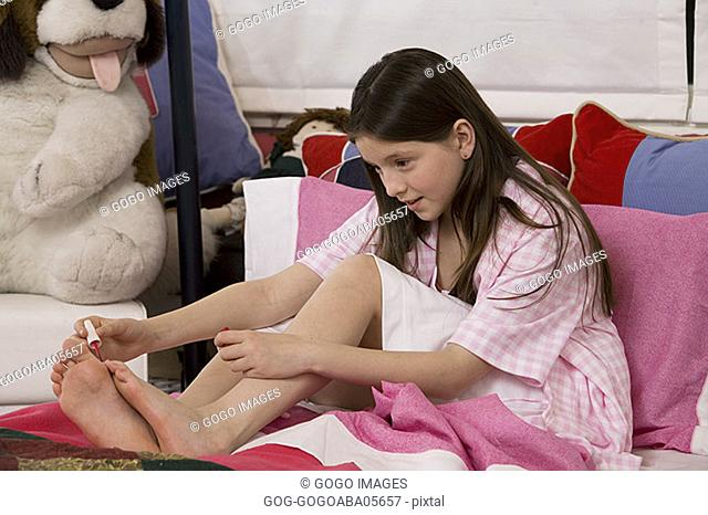 Young girl painting her toenails in bed