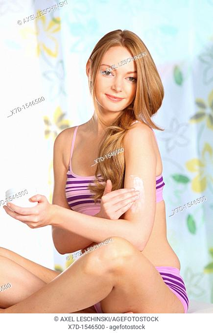 portrait of woman lotion her arm