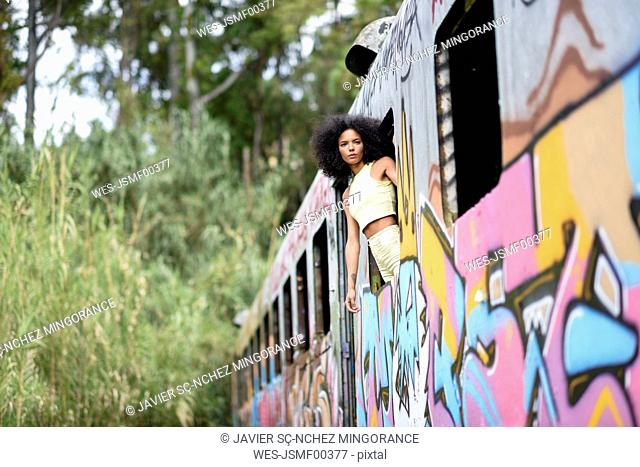 Fashionable young woman leaning out of window of an abandoned and destroyed old train