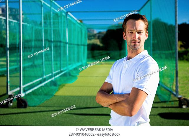 Portrait of young cricketer with arms crossed standing on field