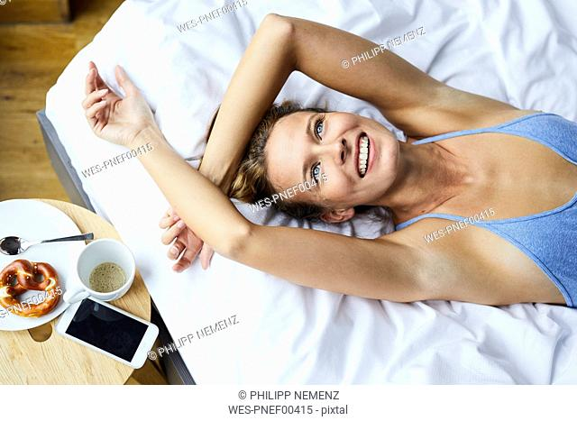 Portrait of laughing young woman lying in bed