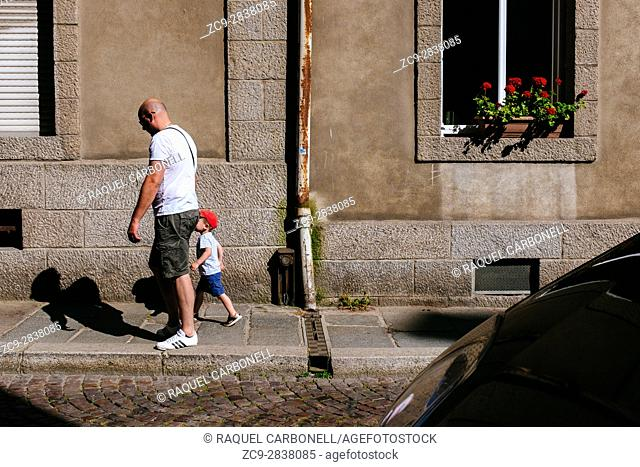 Father and son walking on street passing by stone house window, Saint Malo, Ille-et-Vilaine, Brittany, France