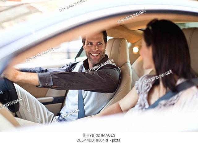 Smiling couple talking in sports car