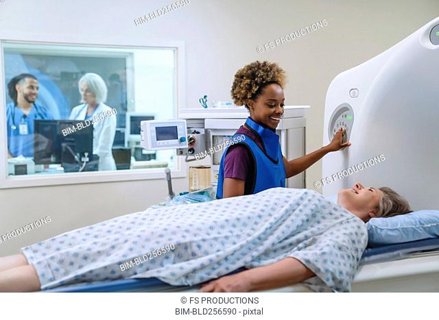 Smiling technician preparing scanner for patient