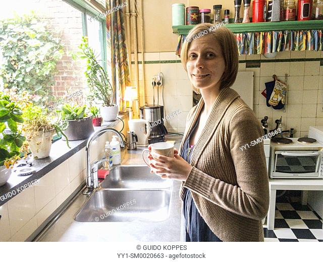 Tilburg, Netherlands. Young adult, caucasian woman drinking a cup of tea, while leaning against her vintage kitchen sink