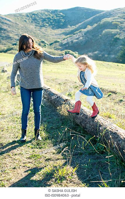 Mid adult woman holding daughter's hand while she jumps from log