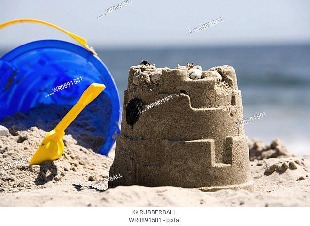Close-up of a sand pail and shovel lying near a sand castle