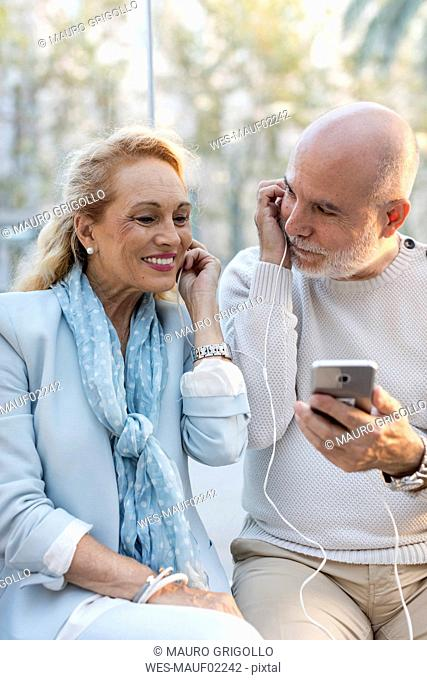 Spain, Barcelona, happy senior couple sharing smartphone with earbuds