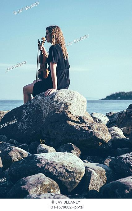 Low angle view of woman with violin sitting on rocks by lake while looking away