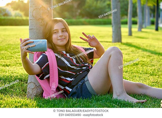 Blond student kid girl with smartphone in a park back to school sit on grass