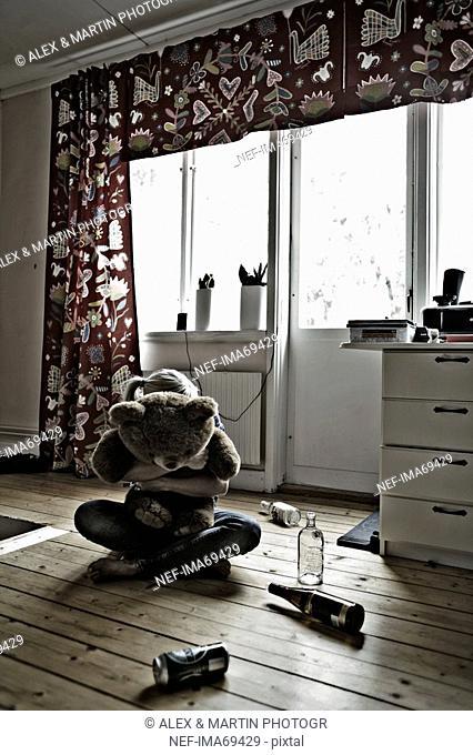 Girl sitting on the floor, hugging her teddy bear, Sweden