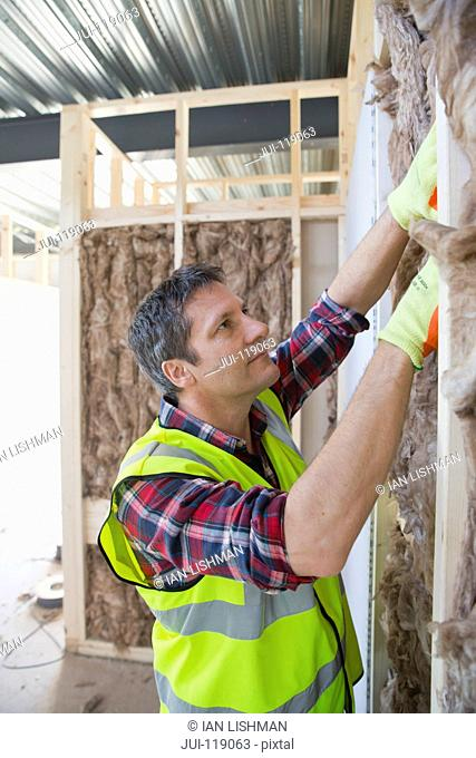 Builder fitting insulation fibre to room walls