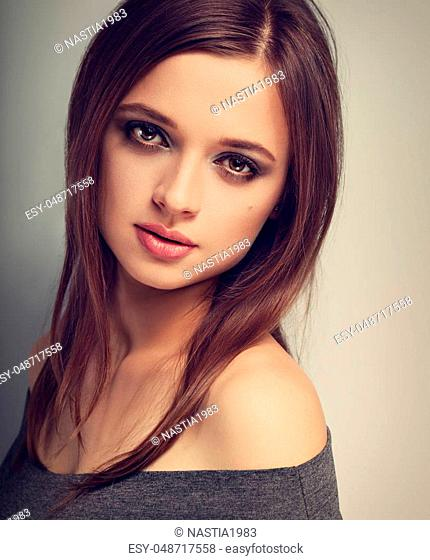 Beautiful expression natural emotion woman with bright makeup looking calm with long smooth hair. Toned vintage closeup portrait