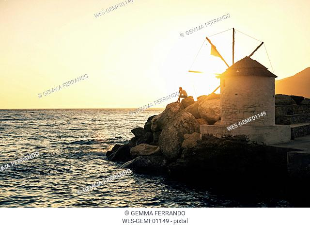 Greece, Amorgos, Aegialis, silhouette of man sitting near wind mill at sunset