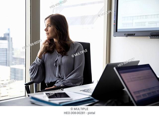 Pensive businesswoman looking out conference room window