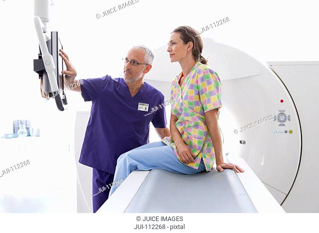 Doctor and patient reviewing results on computer monitor at CT scanner in hospital