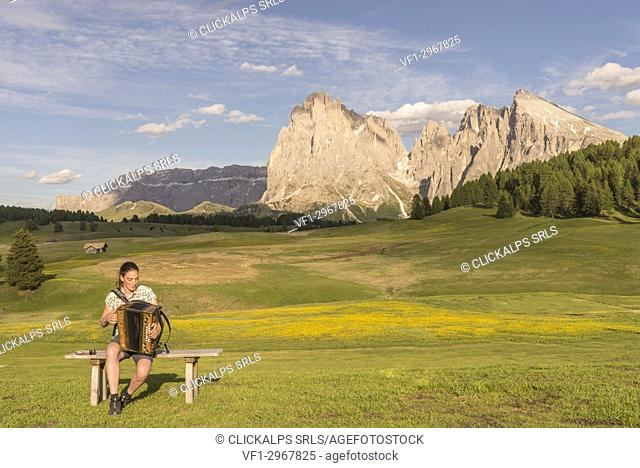 Alpe di Siusi/Seiser Alm, Dolomites, South Tyrol, Italy. Young woman playing with the accordion at the Alpe di Siusi