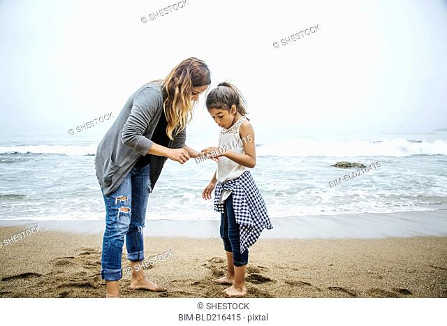 Hispanic mother and daughter standing barefoot on beach