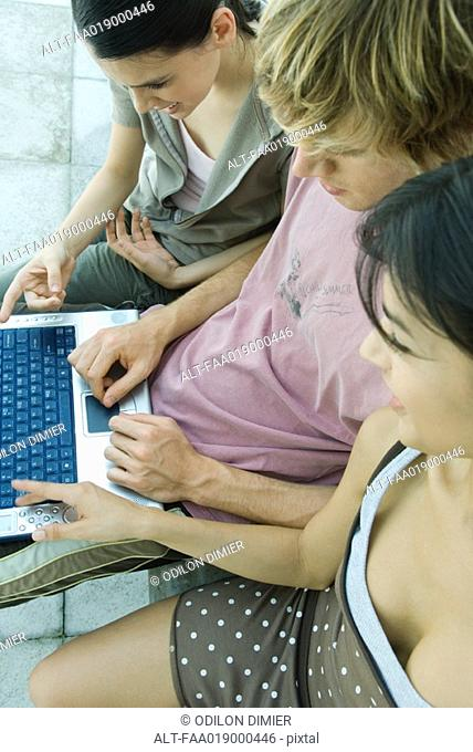 Young friends using laptop together, high angle view