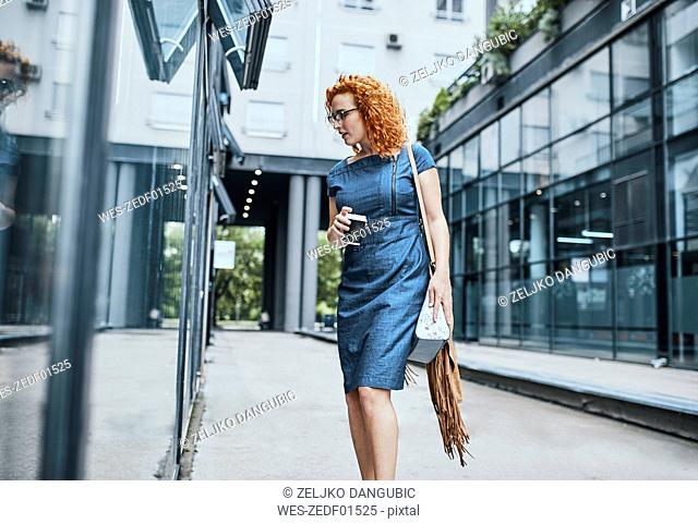 Young businesswoman window shopping in the city, carrying take out coffee