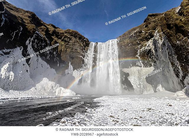 Frozen Skogafoss Waterfall with rainbow, Iceland