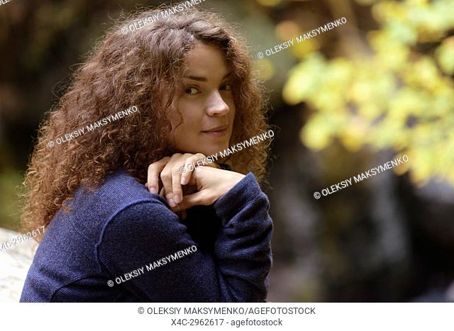 Candid natural portrait of a young woman with long brown hair and cute smiling expression on her face in fall nature scenery