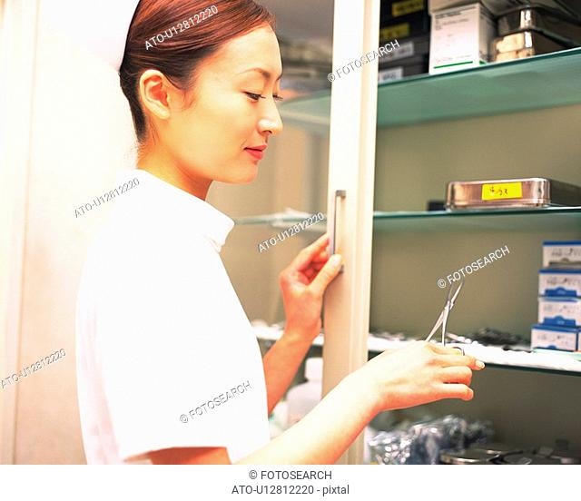 Nurse taking scissors from a surgical equipment of shelf