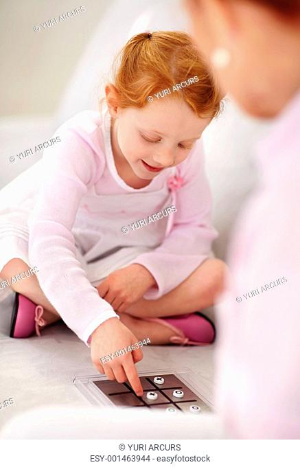 Portrait of a granddaughter playing tic tac toe game with her grandmother