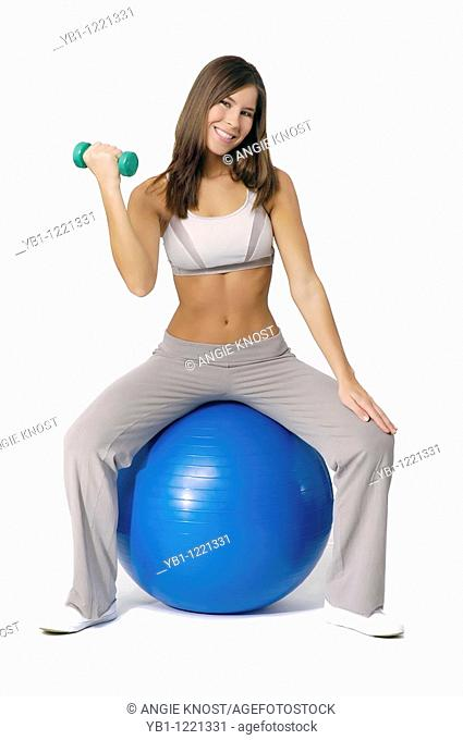 Attractive, fit woman sitting on exercise ball and using handweight