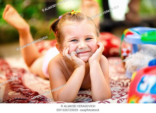 Happy smiling baby girl lying on a blanket outdoors. Little girl resting his head on his hands and looking into the camera. Shallow depth of field