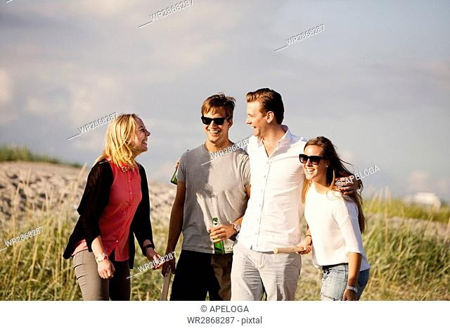 Cheerful young friends playing kubb game at beach