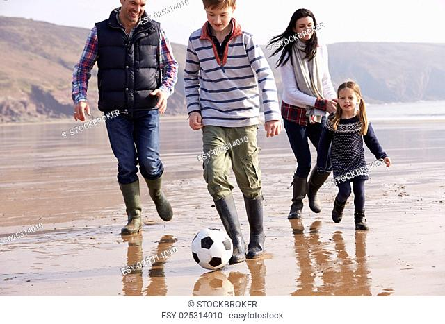 Family Playing Football On Winter Beach