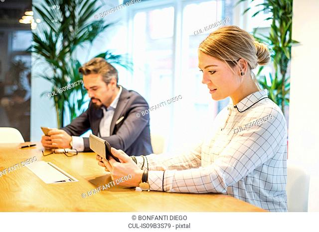 Businesswoman and man at office desk looking at digital tablet and smartphone