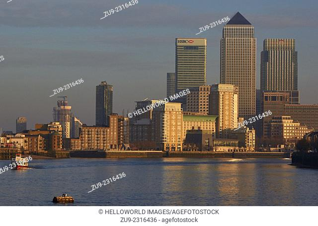 River cruise boat on the Thames near Canary Wharf at sunset, east London, England, Europe