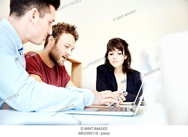 Three people seated at a table at a business meeting using and sharing a laptop screen