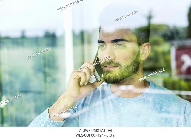 Young man with cell phone looking out of window