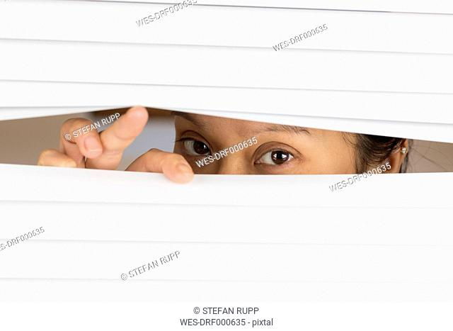 Woman peeking from behind blinds