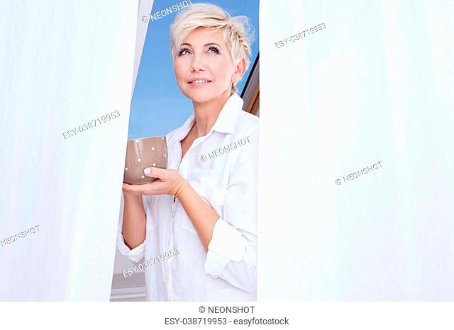 Attractive adult woman drinking hot coffee at the morning