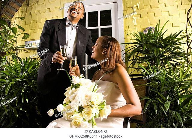 Happy African American bride and groom toasting champagne glasses on outdoor patio on wedding day