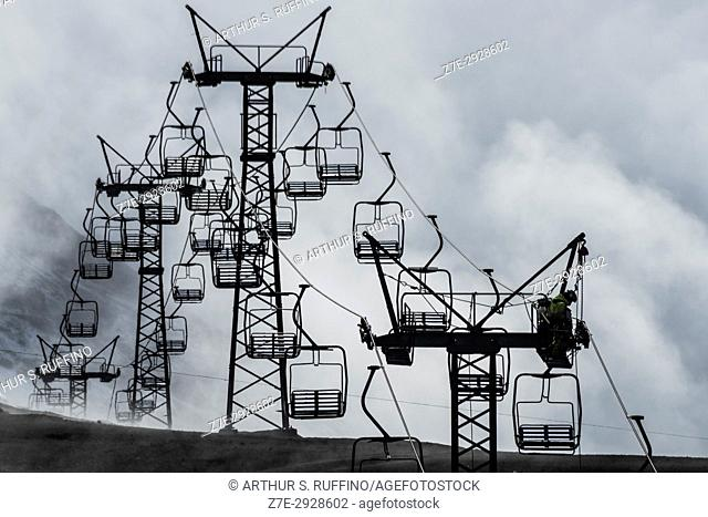 Ski lifts enshrouded in fog following an abrupt change in weather from sunny to light snow flurries. Osorno Volcano Ski Center, Lake District (Los Lagos Region)