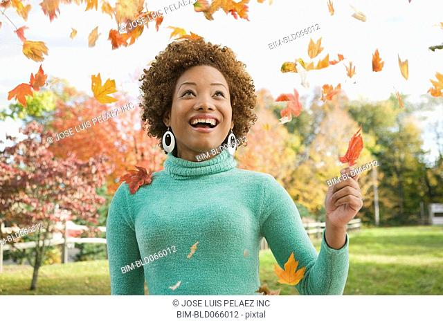 Hispanic woman watching falling autumn leaves