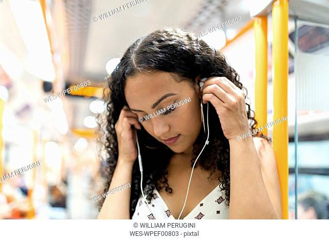 Young woman listening to music with earphones on the subway train