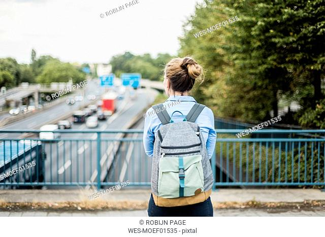 Rear view of woman with backpack on motorway bridge